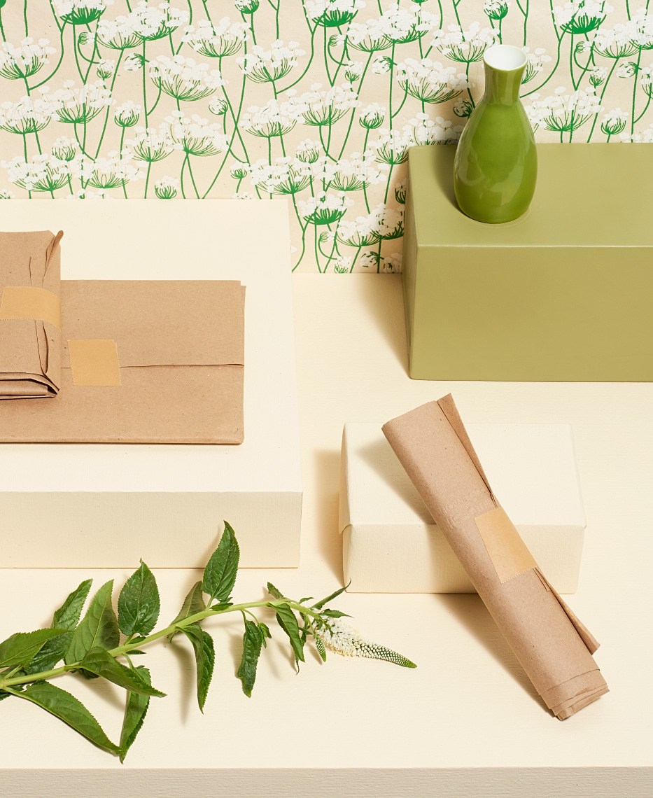 objects on various cream colored boxes with floral wallpaper background still life