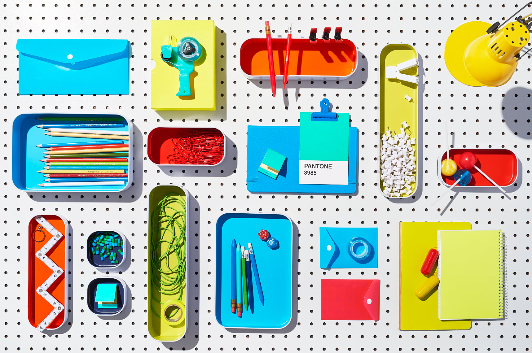 Overhead colorful containers from The Container Store on white pegboard