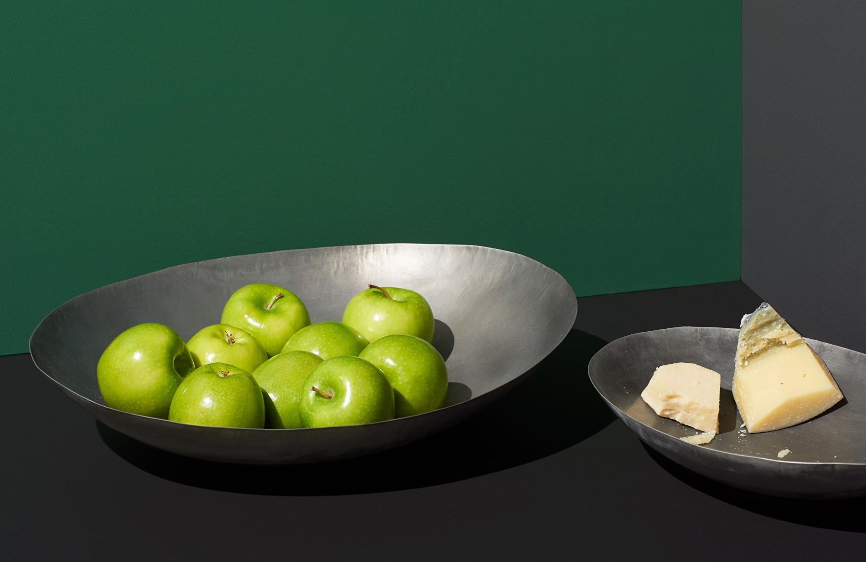 large organic metal bowl with green apples and cheese