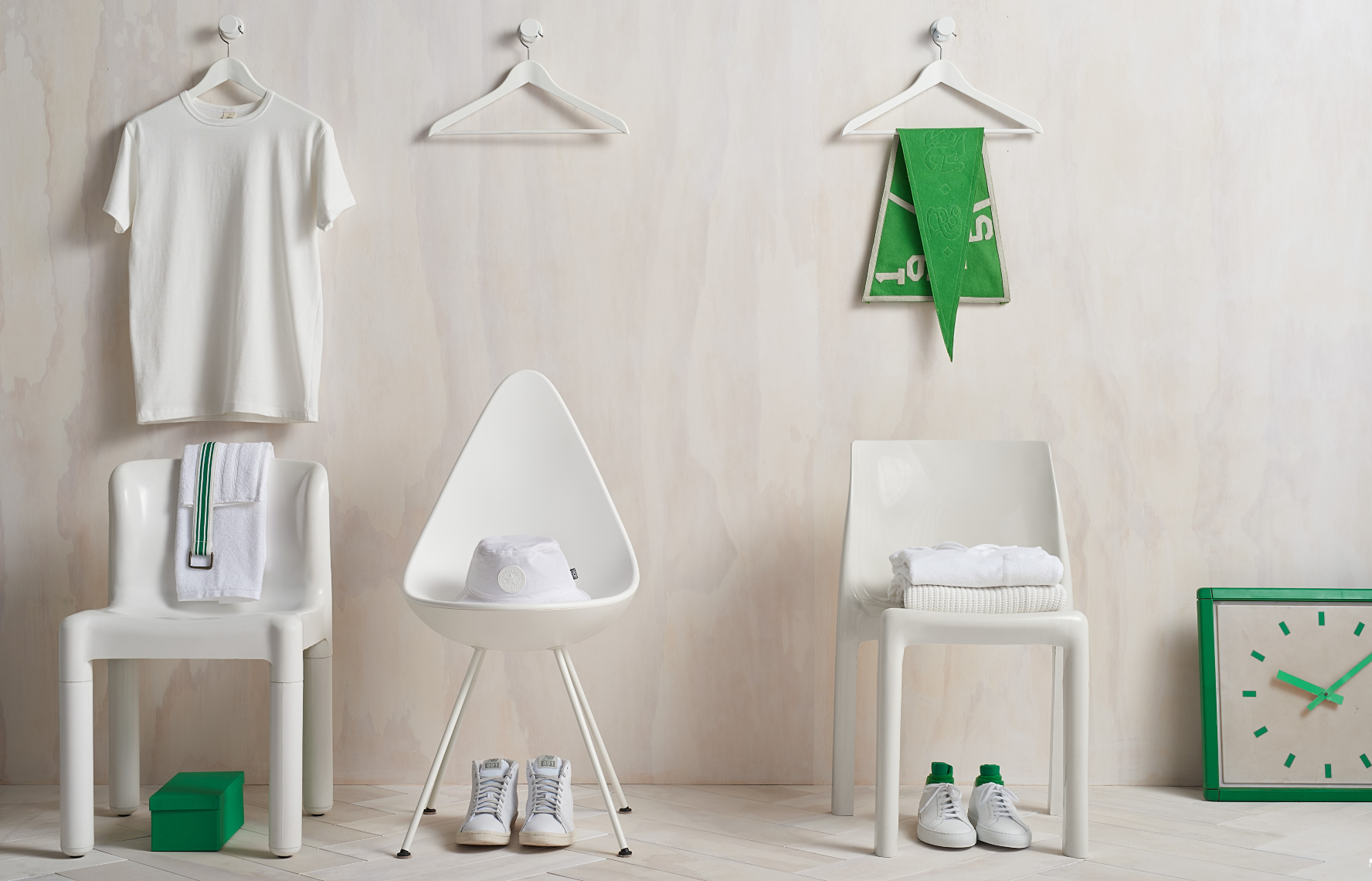 3 white plastic modern chairs with white props against white washed wood wall and white washed floor