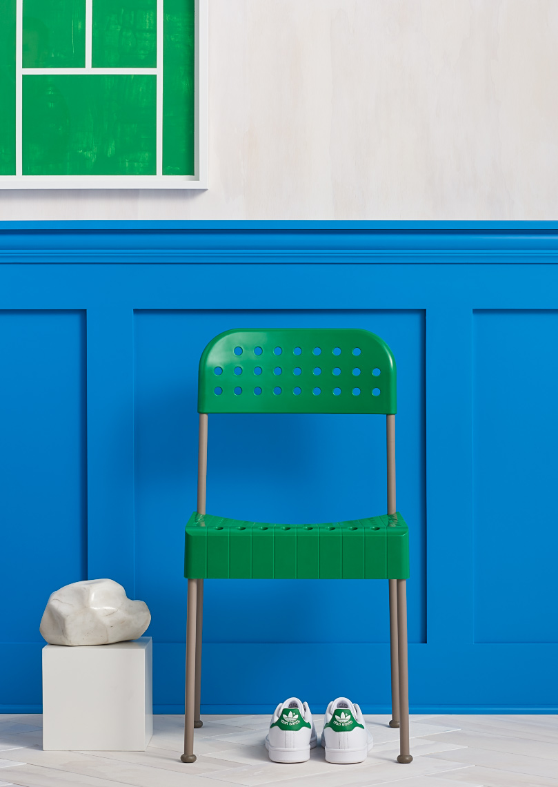 green plastic modern chair with bright blue paneled wall and adidas shoes