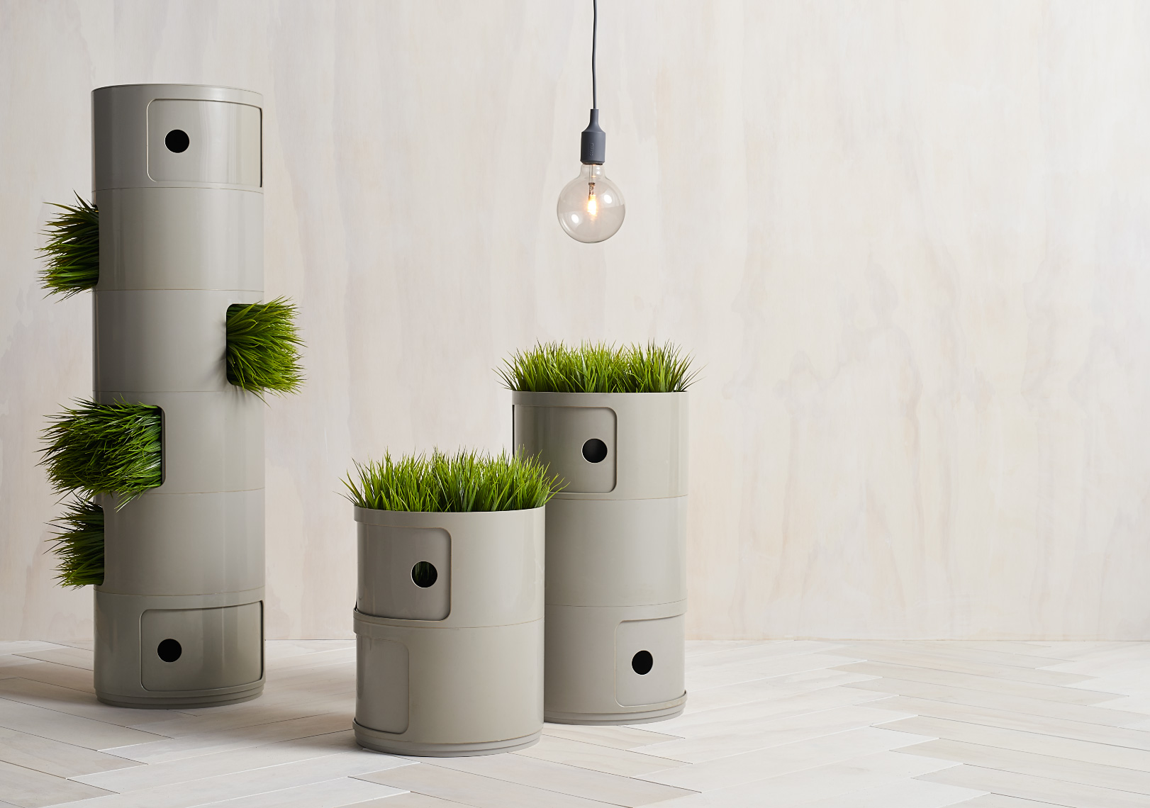 gray stackable plastic drawers with green grass against white washed wall and herringbone floor