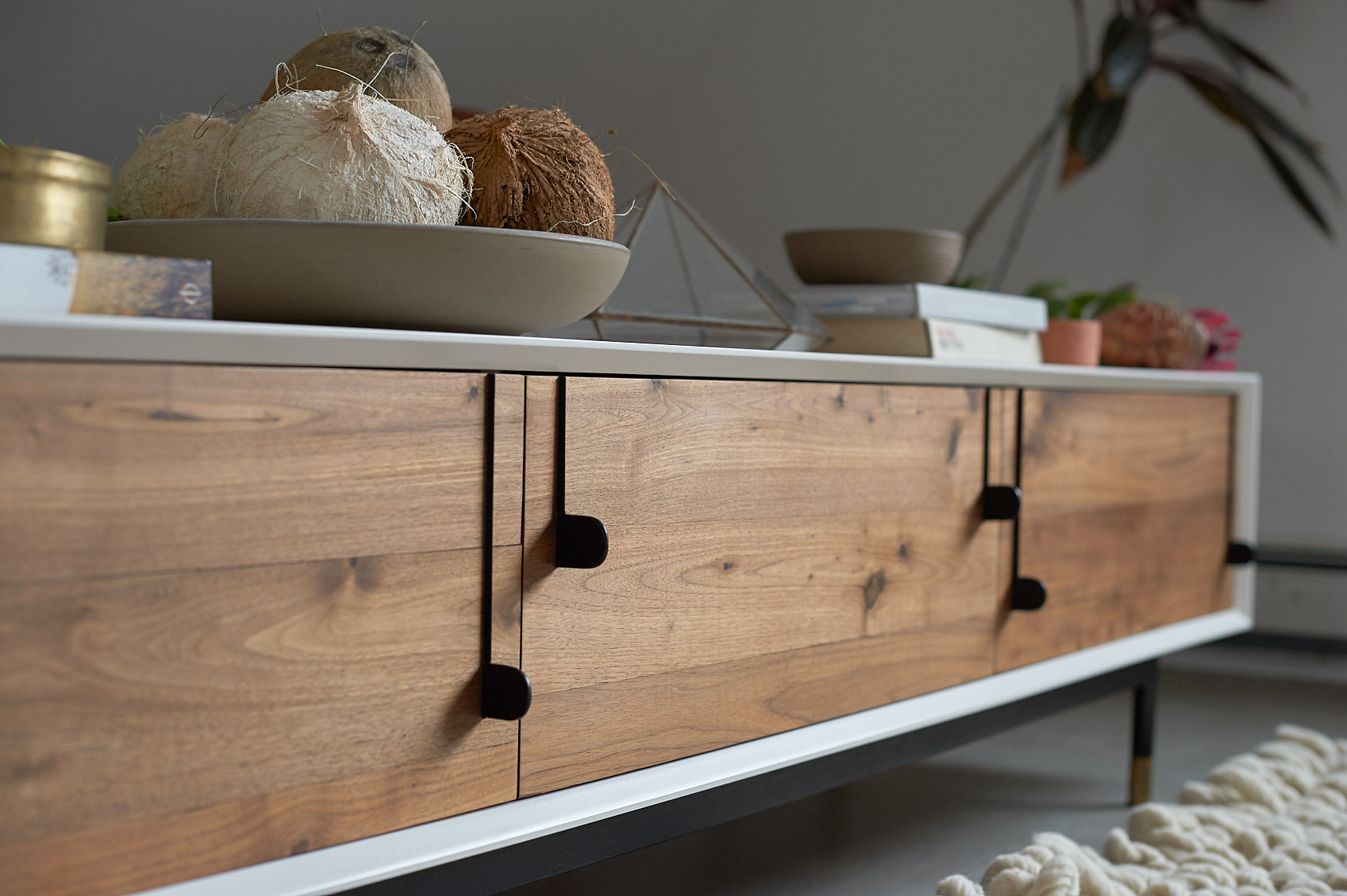custom walnut credenza with white edges and black vertical pulls propped with coconuts