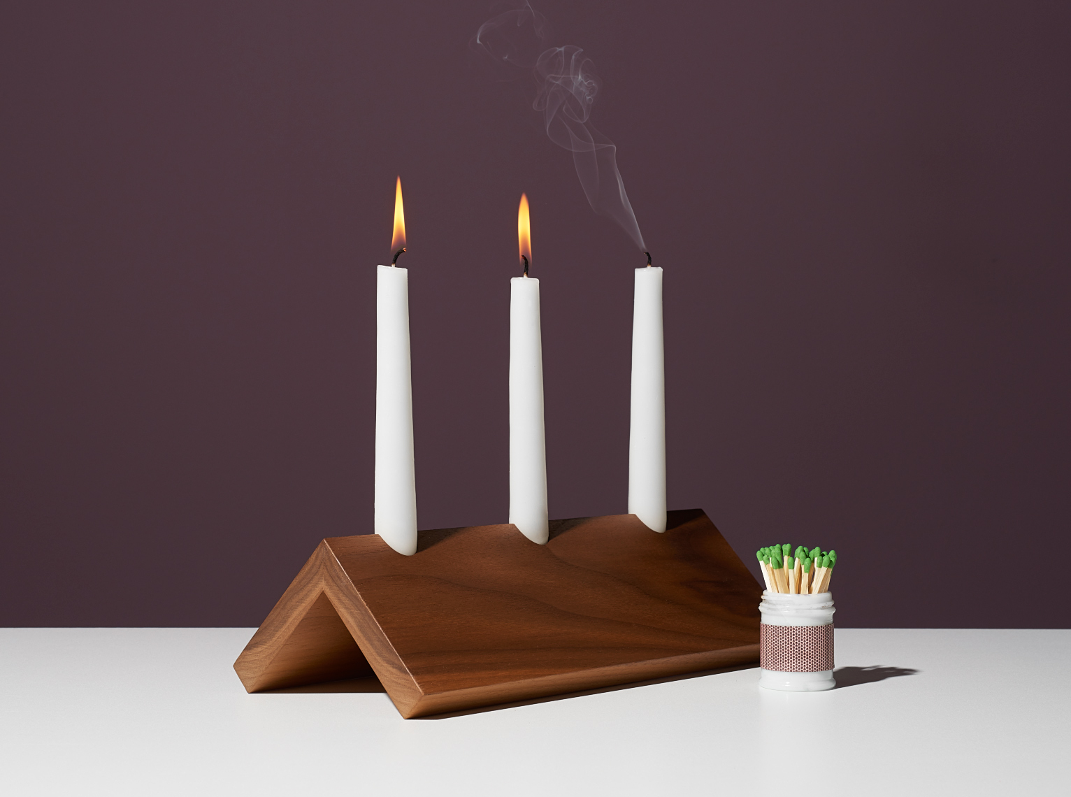 modern walnut a frame taper candle holder with 2 white candles with flame and 1 candle blown out with smoke