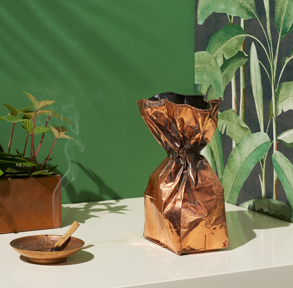 cooper sculpture of paper bag with copper incent holder burning Palo Santo stick against palm leaf wallpaper