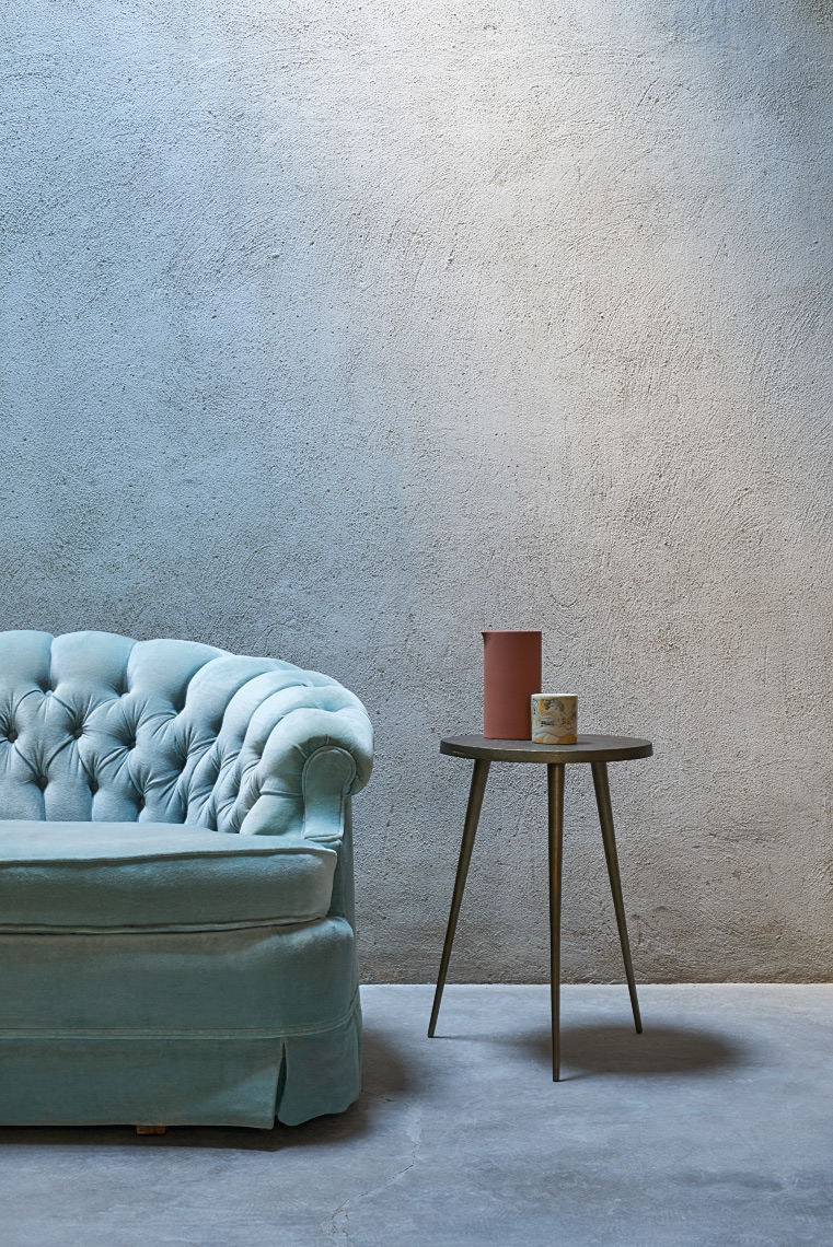 cement wall and floor with blue tufted sofa and 3 legged side table with ceramic pitcher mixed blue light