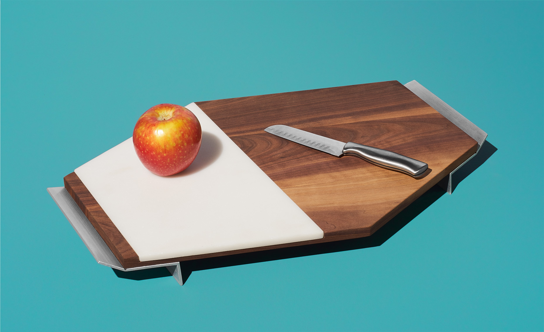 Tandem Made walnut and marble cutting board with apple and knife on aqua surface