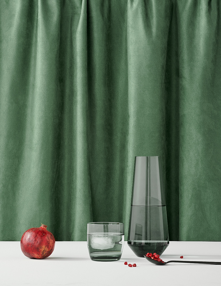 Pomegranate on white surface with smoke glass cup and pitcher and spoon green background still life photo